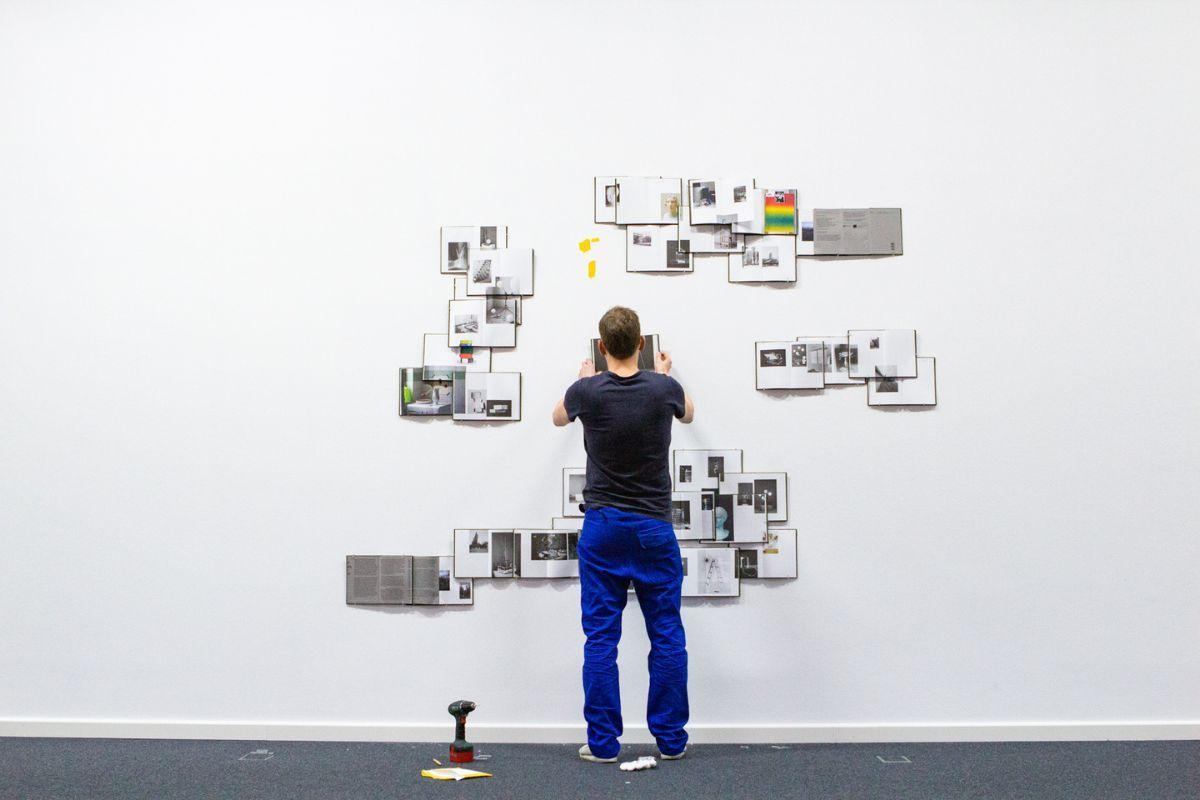 """der Künstler Peter Puklus, wie er 35 Exemplare seines Buches """"Handbook to the Stars"""" an einer Wand im Wilhelm-Hack-Museum in Ludwigshafen für die Ausstellung der Biennale für aktuelle Fotografie 2020 installiert"""