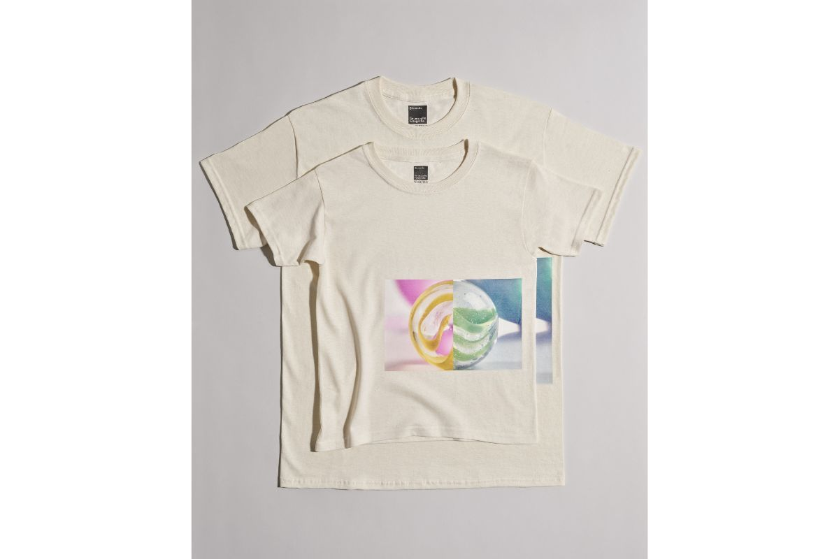 two light-coloured T-shirts, one on top of the other. The upper T-shirt is smaller than the lower one. A photo is printed on the T-shirt. The photo shows a colourful glass marble made up of two halves.