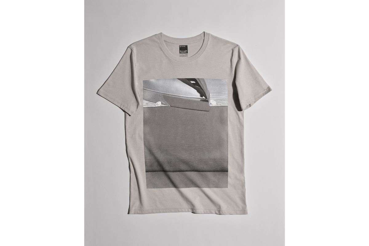 a grey T-shirt with a photo printed on it. The photo shows the tip of an iron being used to iron a shirt.