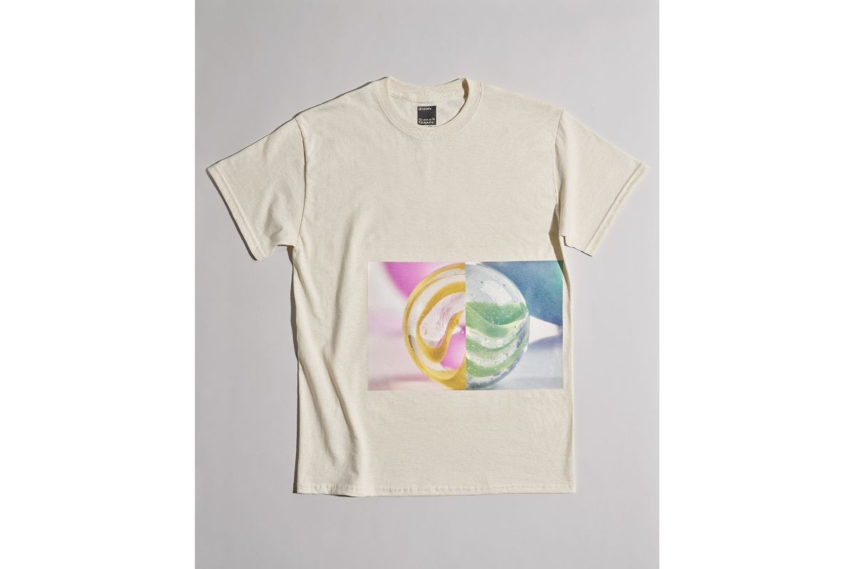 a light-coloured T-shirt with a photo printed on it. The photo shows a colourful glass marble composed of two halves.